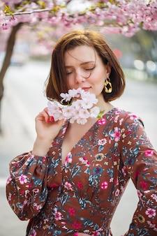 Una donna spettacolare in un vestito luminoso si erge sullo sfondo di sakura. una donna dai capelli scuri in un bellissimo vestito sorride per strada mentre cammina