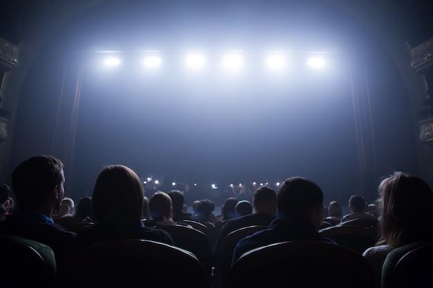 Gli spettatori aspettano l'inizio del concerto seduti sulle sedie dell'auditorium.