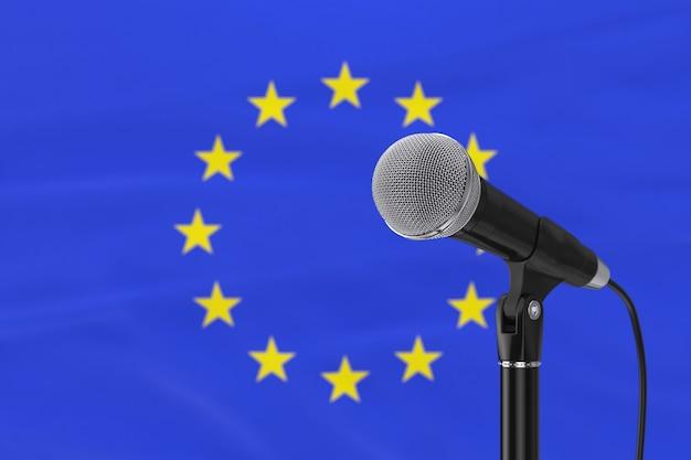 Supporto del microfono vocale contro il primo piano estremo sfocato della bandiera dell'unione europea. rendering 3d