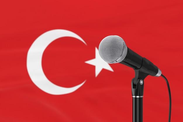 Supporto del microfono vocale contro il primo piano estremo sfocato della bandiera turca. rendering 3d
