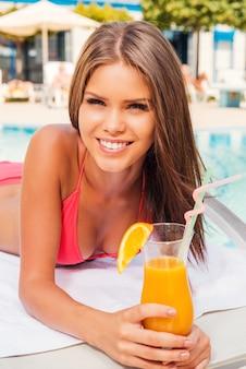 Trascorrere del tempo spensierato a bordo piscina. bella giovane donna in bikini che tiene cocktail e sorride mentre si rilassa sulla sedia a sdraio vicino alla piscina