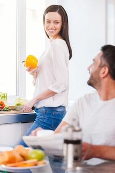 Passare il buongiorno insieme. bella giovane coppia che trascorre del tempo in cucina insieme
