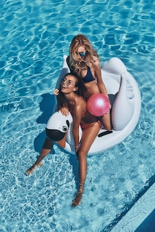 Trascorrere un ottimo periodo estivo. vista dall'alto di due belle giovani donne in bikini che sorridono mentre galleggiano su un grande cigno gonfiabile