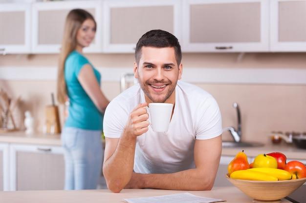 Trascorrere una bella mattinata insieme. bel giovane appoggiato al fornello della cucina e tenendo una tazza di caffè mentre bella donna in piedi sullo sfondo e sorridente