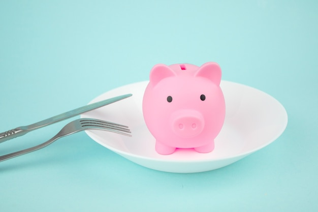 Concetto di risparmio di spesa, salvadanaio su piatto bianco con forchetta e coltello su sfondo blu