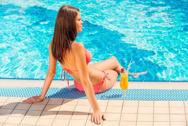 Trascorrere l'estate a bordo piscina. vista posteriore di una giovane donna in bikini seduta a bordo piscina con un cocktail vicino a lei