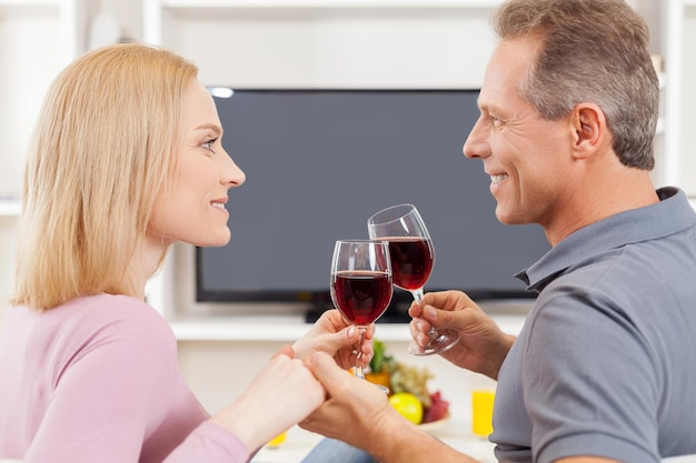 Trascorrere del tempo insieme. vista laterale di una coppia matura allegra seduta davanti alla tv e che si guarda mentre tiene in mano bicchieri di vino rosso