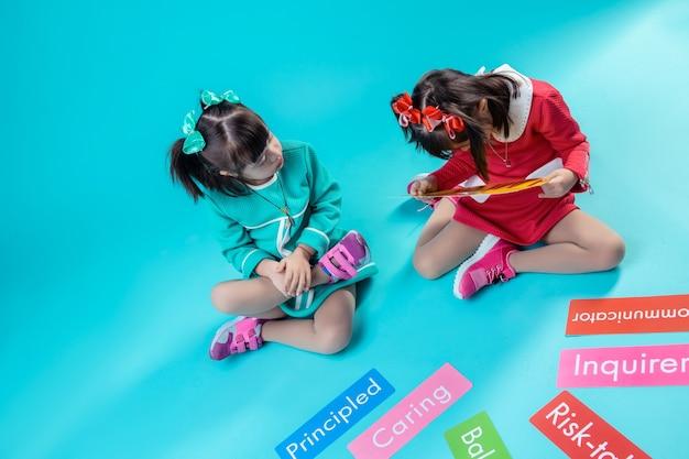 Trascorrere del tempo insieme. due ragazze con sindrome di down sono interessate alle parole sulle targhette mentre erano sedute insieme