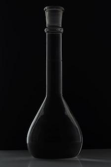 Il pallone sferico riempito con un liquido con un lungo becco su sfondo nero