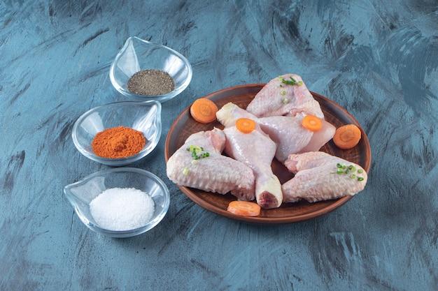 Ciotole di spezie e carne di pollo su un piatto di legno, sulla superficie blu.