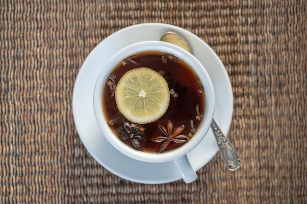 Tè speziato, composto da cannella, pepe nero, cardamomo, anice stellato, limone, chiodi di garofano e succo di mela caldo. primo piano, vista dall'alto. tè alla cannella. bere il tè