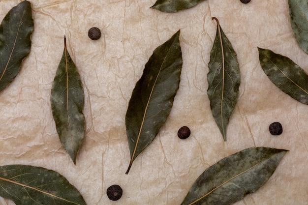 Struttura della spezia con foglie di alloro e palline di pepe nero. su un bellissimo sfondo rustico alla vaniglia. vista dall'alto