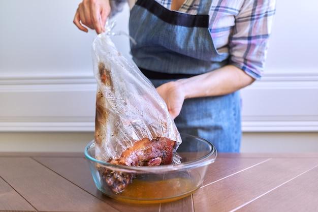 Coscia di maiale marinata speziata nella manica da forno, donna che prende carne calda al forno dalla borsa da cucina