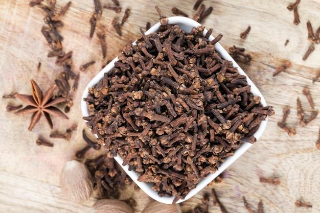 Spezie di chiodi di garofano sparse su un vecchio tavolo di legno in cucina, spezie profumate di chiodi di garofano vengono utilizzate in cucina durante la preparazione di carne e altri piatti e conserve