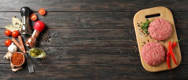 Spezie e tagliere con carne tritata su legno, spazio per il testo
