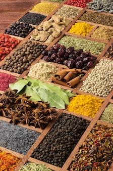 Sfondo di spezie ed erbe aromatiche. sapori da tutto il mondo. condimenti colorati per cucinare cibi gustosi. condimenti in cassetta di legno.