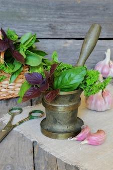 Spezie ed erbe aromatiche in mortaio e cesto su uno sfondo di legno scuro
