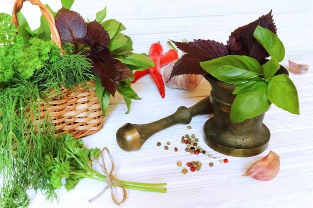 Spezie ed erbe aromatiche in mortaio e cesto su uno sfondo di legno chiaro