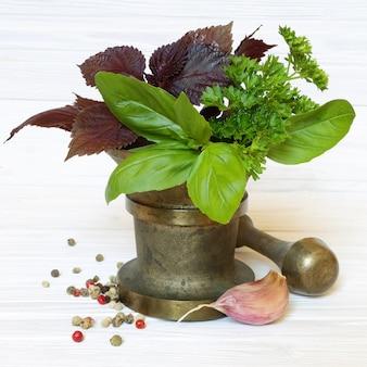 Spezie ed erbe aromatiche in mortaio su fondo in legno chiaro