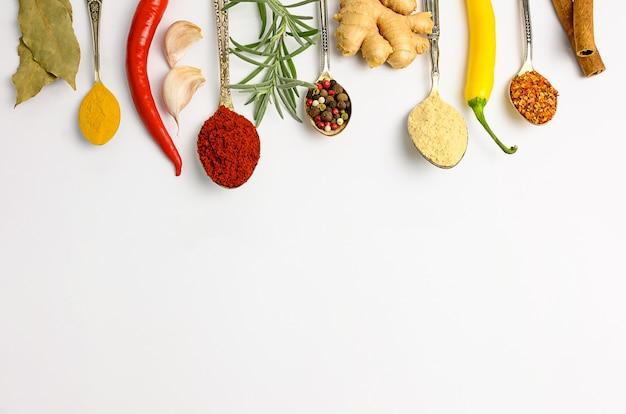 Spezie ed erbe aromatiche in vecchi cucchiai su sfondo bianco