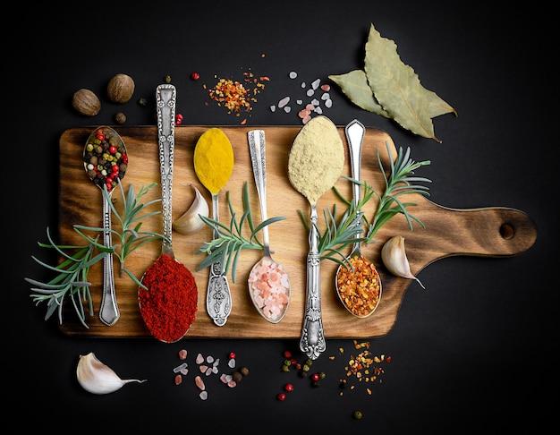 Spezie ed erbe aromatiche in vecchi cucchiai sul bordo di legno sfondo nero
