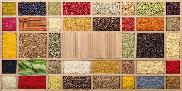 Spezie ed erbe aromatiche in una scatola di legno, vista dall'alto. condimenti da tutto il mondo per la cottura dei cibi.