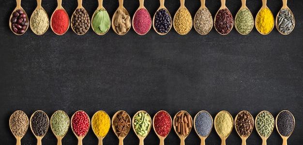 Spezie ed erbe aromatiche in cucchiai di legno. raccolta di spezie con uno spazio vuoto per un'iscrizione o un'etichetta.