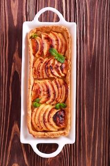 Crostata di mele piccante sulla piastra sul tavolo di legno