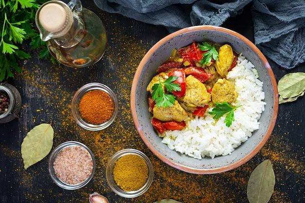 Pollo al curry piccante con riso. salsa al curry con pollo e riso su sfondo scuro. vista dall'alto