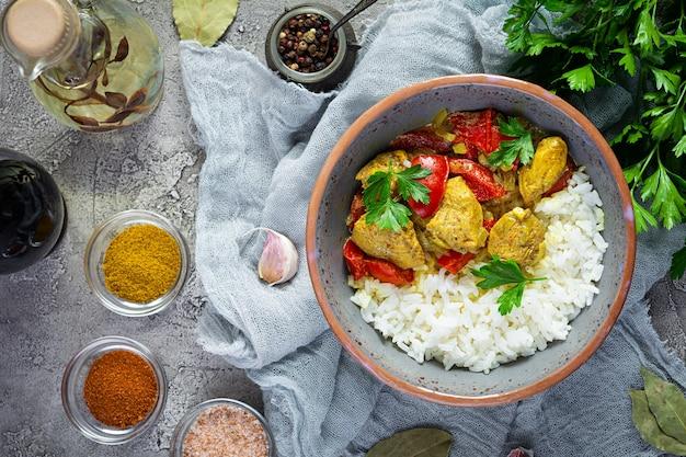 Pollo al curry piccante con riso. salsa al curry con pollo e riso su sfondo grigio. vista dall'alto