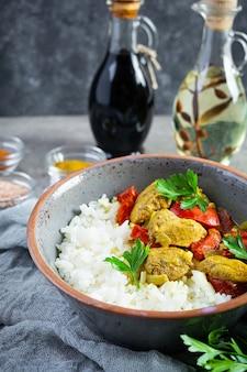 Pollo al curry piccante con riso. salsa al curry con pollo e riso su sfondo grigio