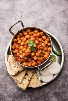 Curry piccante di ceci, chana masala o choley in una ciotola con chapati e insalata. piatto tipico dell'india settentrionale.