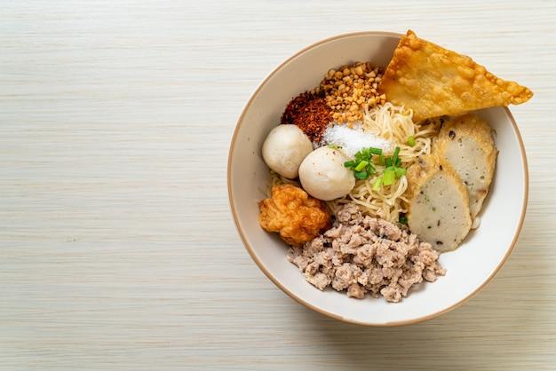 Tagliatelle piccanti all'uovo con polpette di pesce e polpette di gamberi senza zuppa. stile di cibo asiatico