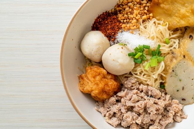 Tagliatelle piccanti all'uovo con polpette di pesce e polpette di gamberi senza zuppa - stile di cibo asiatico