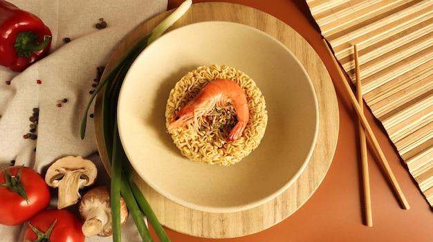 Zuppa di noodle istantanei piccante con gamberi e verdure. zuppa di gamberetti, cucina, cibo. vermicelli a forma di cerchio essiccati crudi in un piatto pasta, per la cui preparazione è sufficiente versare acqua bollente.