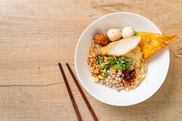 Tagliatelle piccanti con polpette di pesce e carne di maiale tritata (tom yum noodles) - stile di cibo asiatico