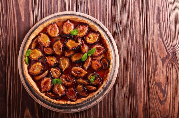 Torta piccante crostata di prugne su tavola di legno
