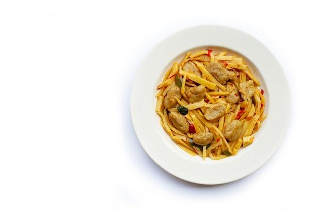Ricetta fritta scalpore conservate piccanti del germoglio di bambù con la palla di pesce su fondo bianco.