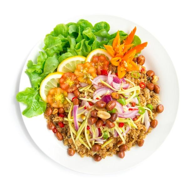 Insalata piccante pesce gatto croccante con fetta di mango cibo gustoso caldo di thai in cima arachidi fritte decorare con peperoncino di quercia verde intagliato e vista dall'alto di limone isolato su sfondo bianco
