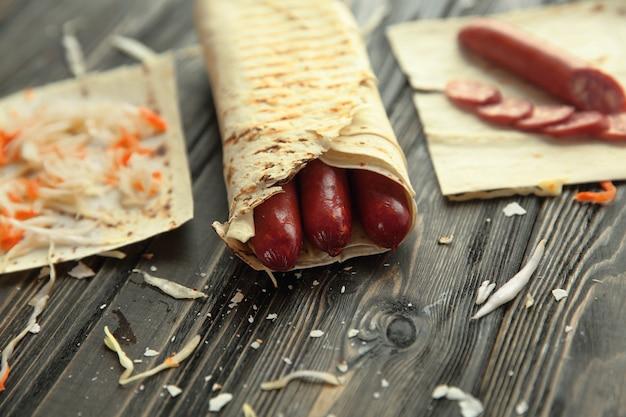 Salsicce piccanti in pane pita su un tavolo di legno.