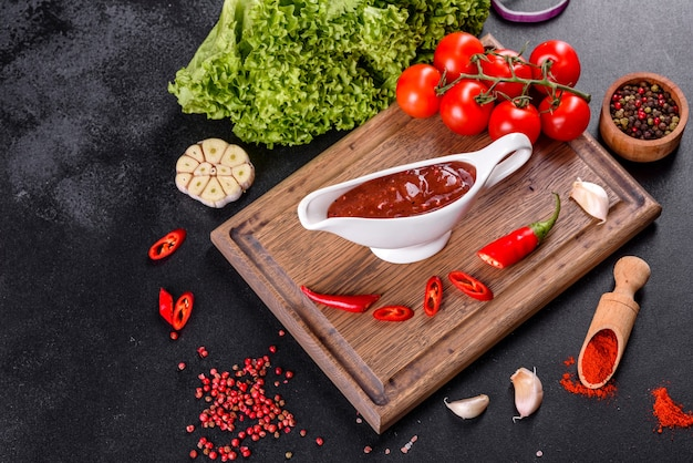 Condimento piccante della cucina georgiana adjika in una ciotola con pepe rosso e aglio su un primo piano di un tavolo di cemento