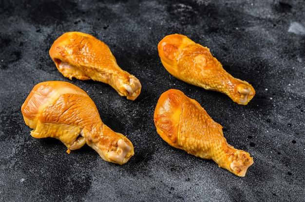 Piccante cosce di pollo affumicate cosce su un tavolo da cucina sulla tavola nera. vista dall'alto.