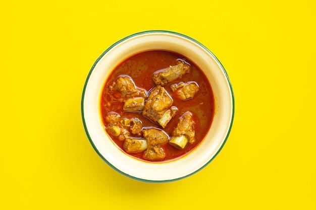 Sparerib di maiale fritto in padella piccante con pasta di peperoncino thai southern in una ciotola di zinco su giallo