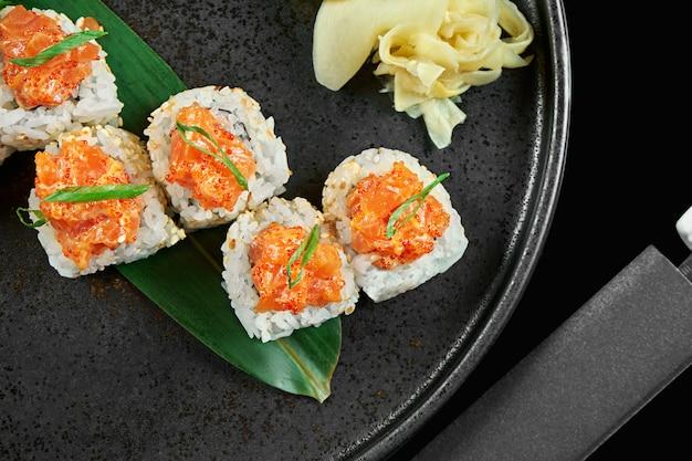 Involtini di sushi piccanti con riso, norme, maionese, caviale tobiko e salmone su un piatto di ceramica nera su una superficie nera. cibo tradizionale giapponese.