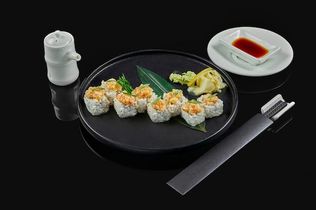 Involtini di sushi piccanti con riso, norme, maionese, caviale tobiko e capesante su un piatto di ceramica nera su una superficie nera. cibo tradizionale giapponese.