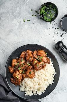 Pezzi di filetto di pollo teriyaki piccante con riso, cipolle verdi e semi di sesamo nero su piastra nera