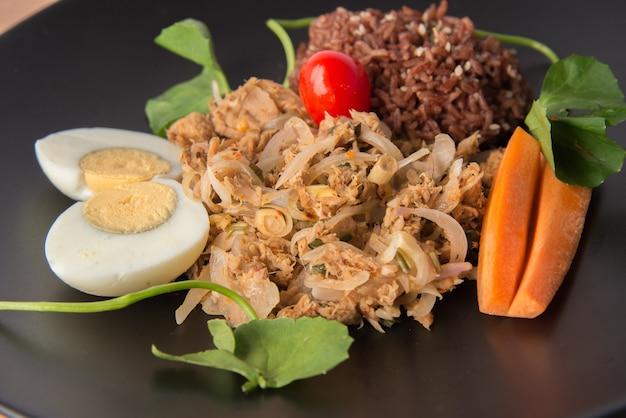 Insalata di tonno piccante con riso integrale e cibo pulito con uova sode