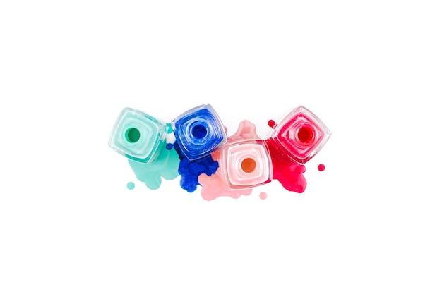Smalto per unghie colorato rovesciato isolato su sfondo bianco flat top view copy space Foto Premium