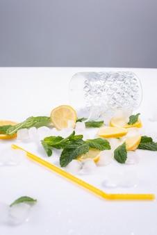 Bicchiere rovesciato di rinfrescante cocktail estivo con ghiaccio, limone e menta su sfondo bianco.