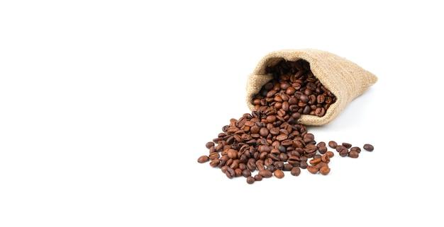 Fuoriuscita di chicchi di caffè da un sacchetto di lino isolato su uno sfondo bianco.